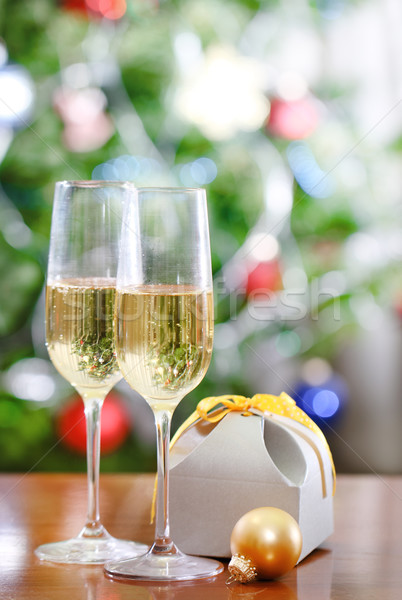 Glasses of champagne and Christmas gift  in front of Christmas t Stock photo © dashapetrenko