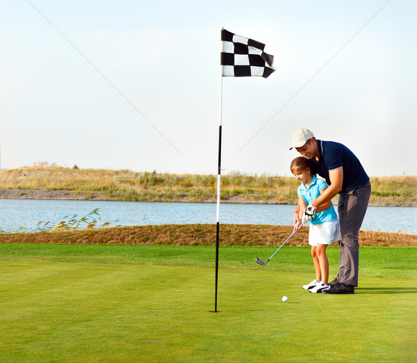Father teaching daughter to play golf on putting on green Stock photo © dashapetrenko