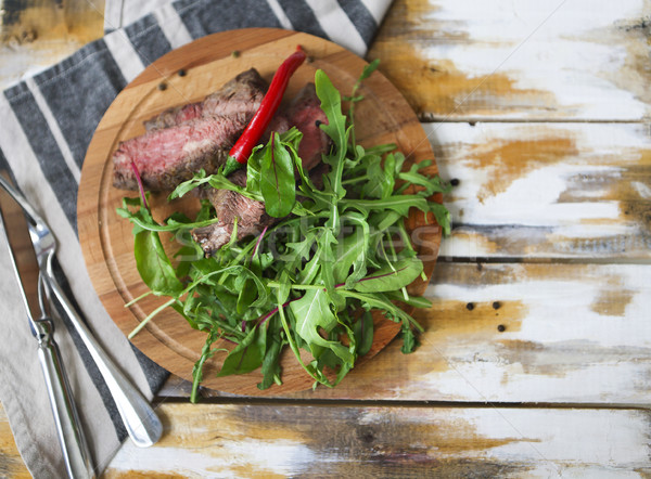 Stock photo: Sliced medium rare grilled Beef steak Ribeye with rocket salad o