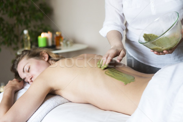 Beautiful relaxed woman having clay mask applying by beautician Stock photo © dashapetrenko