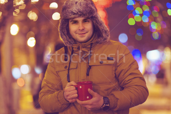 Portrait of young man drinking tea outdoor in wintertime Stock photo © dashapetrenko