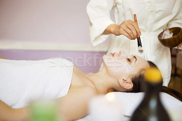 Stock photo: Young woman in a mask for the face of the therapeutic white mud.
