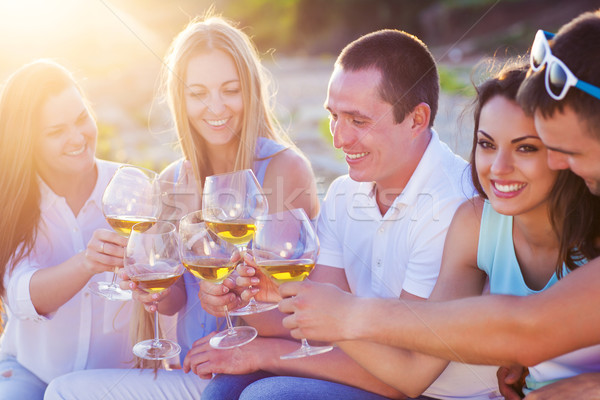 People holding glasses of white wine making a toast at the beach Stock photo © dashapetrenko