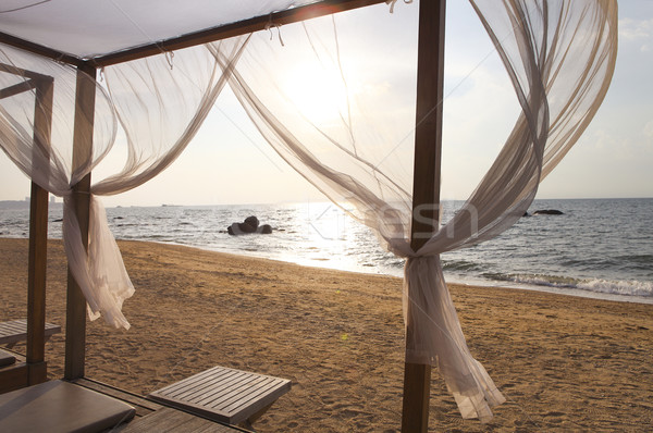 View of a beach in sunset through the curtains of a beach bed Stock photo © dashapetrenko
