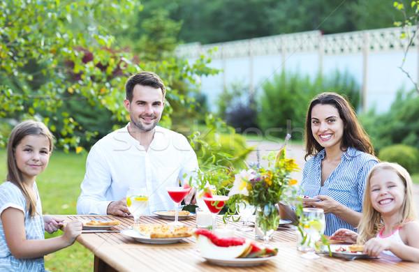 Família feliz quatro pessoas refeição juntos ao ar livre Foto stock © dashapetrenko