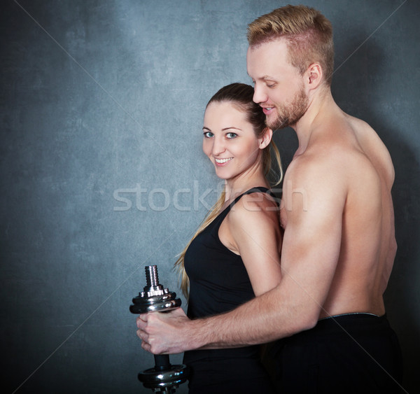 Athletic couple with a dumbells near the wall Stock photo © dashapetrenko