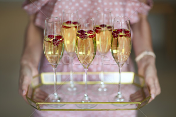 Young woman with champagne glasses on tray Stock photo © dashapetrenko