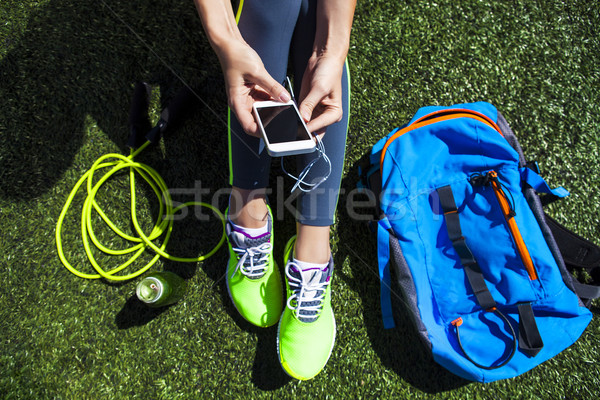 Sporty woman holding phone with empty screen sitting on the gree Stock photo © dashapetrenko