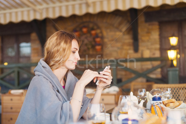 Beautiful young blond woman in plaid with smartphone and espress Stock photo © dashapetrenko