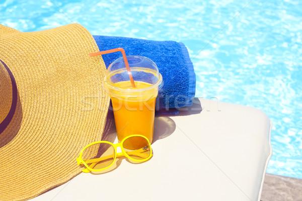 Piscina jugo de naranja toalla de playa gafas de sol sol cama Foto stock © dashapetrenko