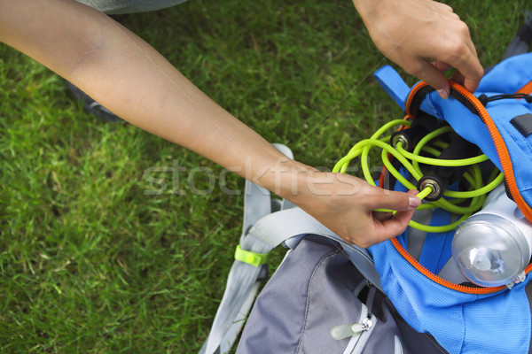 Sporty woman sitting on the green grass with jump rope, backpack Stock photo © dashapetrenko
