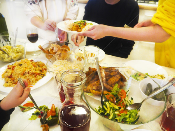 Stock photo: Family having dinner together sitting at the wooden table
