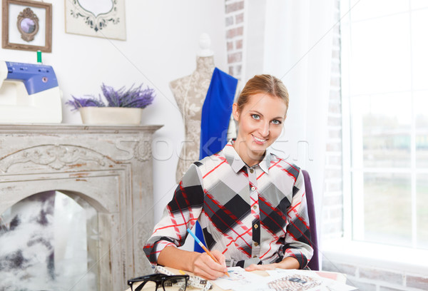 Stock photo: Dressmaker is drawing a fashion sketch