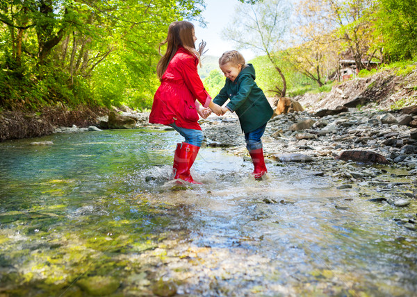 Children wearing rain boots jumping into a mountain river Stock photo © dashapetrenko