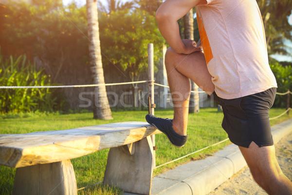 Young fitness man runner stretching legs before run Stock photo © dashapetrenko