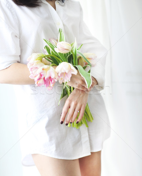 Beautiful young woman holding a bunch of delicate spring pink tu Stock photo © dashapetrenko