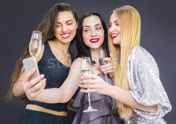 Stock photo: Three young pretty woman having fun and making selfie