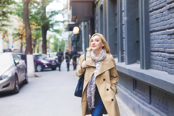 Middle age women goes through the city and smiles. Happiness con Stock photo © dashapetrenko