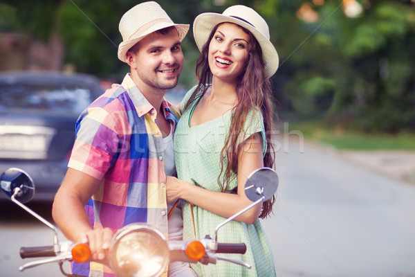 Happy young couple by a vintage scooter in the street wearing ha Stock photo © dashapetrenko