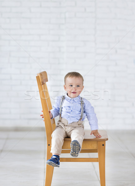 Beautiful adorable laughing baby boy sitting on the chair. Stock photo © dashapetrenko