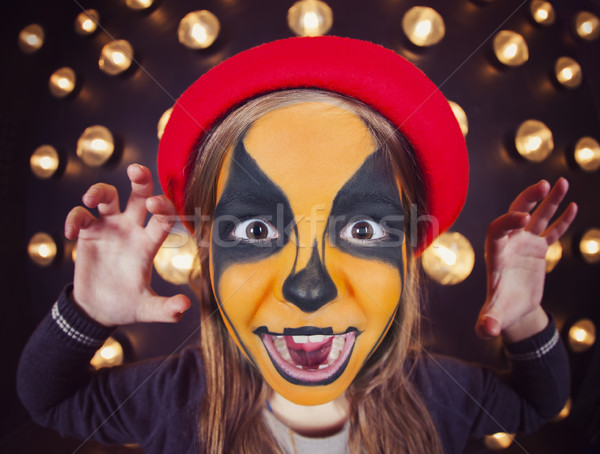 Pretty girl with face painting of a pumpkin  Stock photo © dashapetrenko