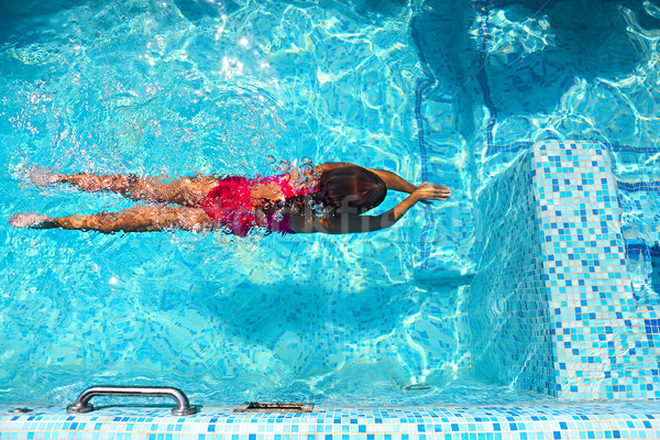 Stock photo: Little girl swimming in the pool