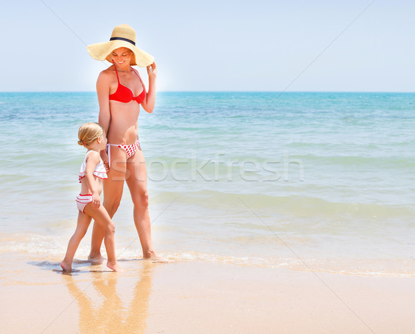 Mother and baby girl running on sea coast Stock photo © dashapetrenko