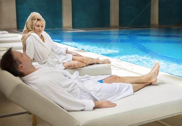 Couple relaxing by the poolside wearing toweling robes Stock photo © dashapetrenko