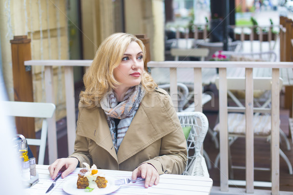 Close up happy adult blond woman in outdoors cafe looking into d Stock photo © dashapetrenko