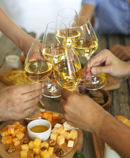 Stock photo: Hands with white wine toasting over served table with food