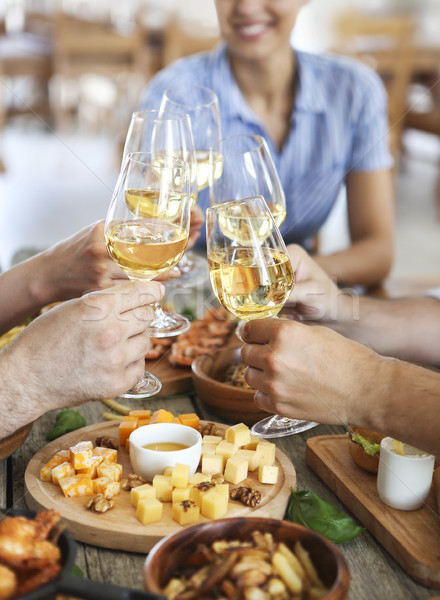 Friends with white wine toasting over served table with food Stock photo © dashapetrenko