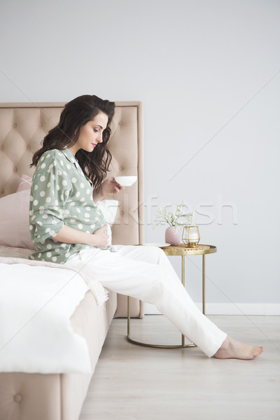 Stock photo: Pregnant young happy woman drinking tea in bed