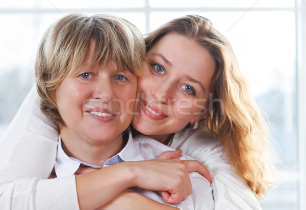 Close up portrait of a mature mother and adult daughter being cl Stock photo © dashapetrenko