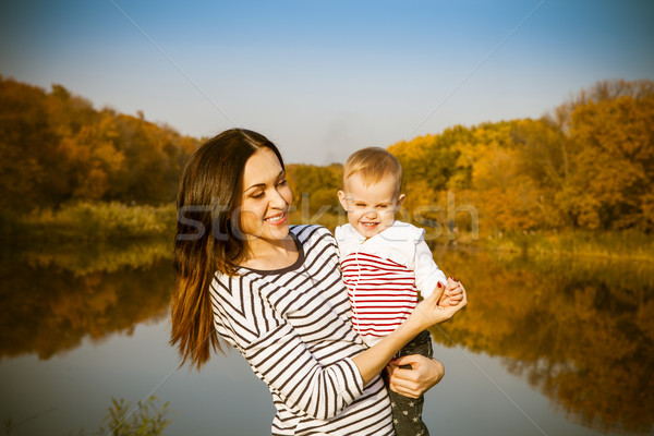 Portrait of smiling mother and baby on lake Stock photo © dashapetrenko