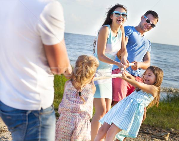 Tug of war - family playing on the beach. Summer holiday  Stock photo © dashapetrenko