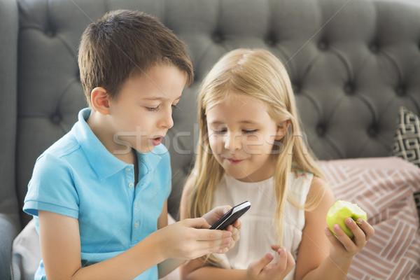 Kicsi fivér lánytestvér kanapé játszik mobiltelefon Stock fotó © dashapetrenko
