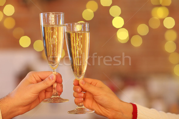 Stock photo: Two glasses of champagne over blur lights background.
