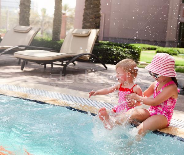 Dois pequeno irmãs jogar piscina água Foto stock © dashapetrenko