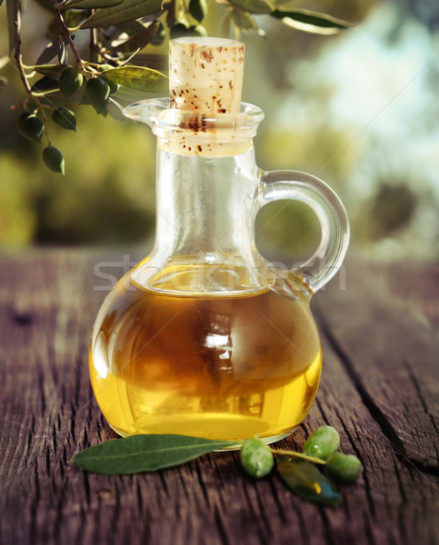 Olive oil and olive branch on the wooden table Stock photo © dashapetrenko