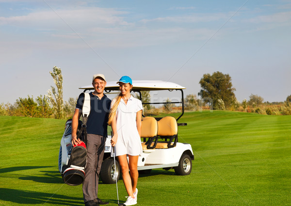 Stock photo: Young sportive couple playing golf on a golf course