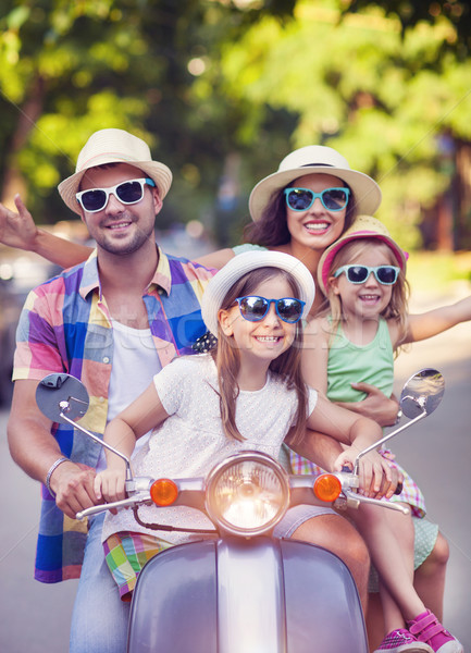 Happy young family riding a vintage scooter in the street wearin Stock photo © dashapetrenko