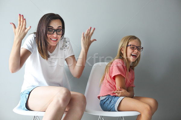 Happy mother and her little daughter sitting on the chairs. Port Stock photo © dashapetrenko