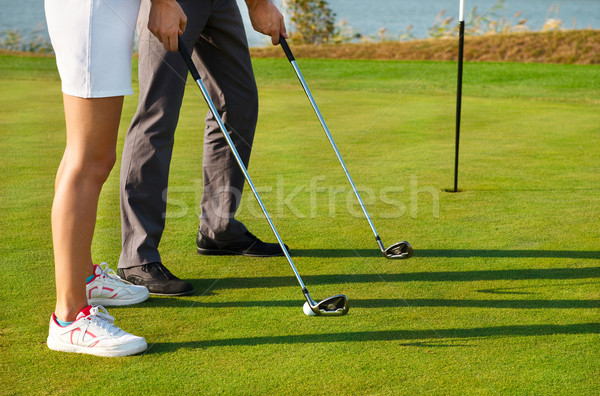 Young sportive couple playing golf on a golf course Stock photo © dashapetrenko