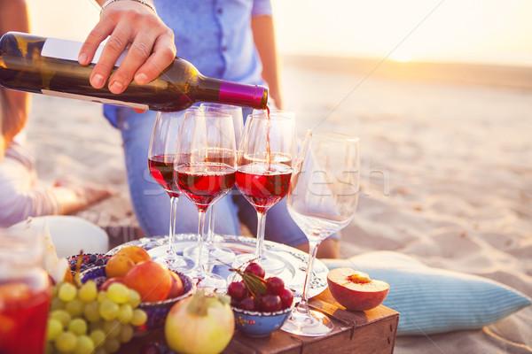 Happy friends having red wine on the beach. Sunset beach party Stock photo © dashapetrenko
