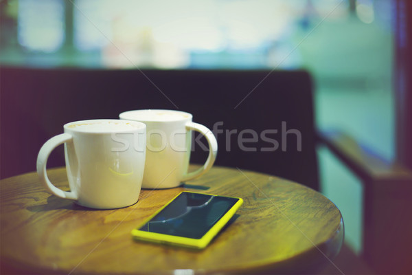 Coffee cups in coffee shop and mobile phone Stock photo © dashapetrenko