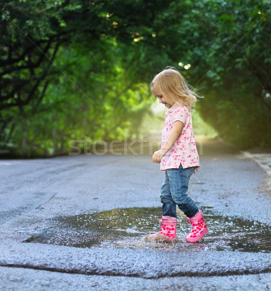 Cute little girl jumping into a puddle Stock photo © dashapetrenko