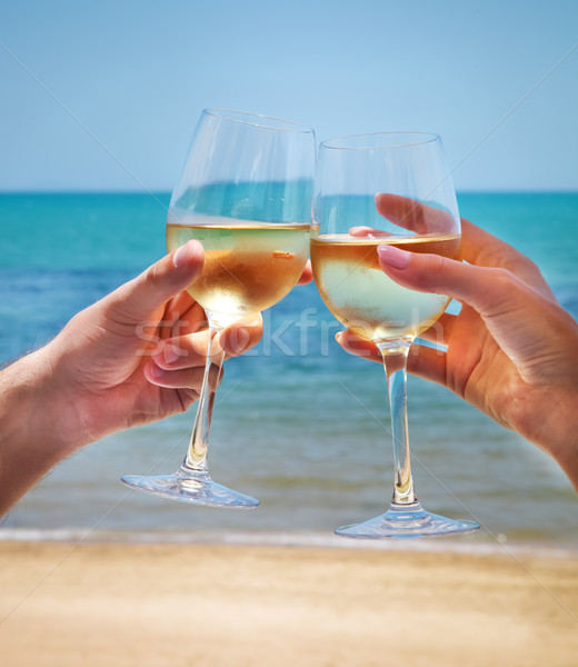 Man and woman clanging wine glasses with white wine at sea backg Stock photo © dashapetrenko