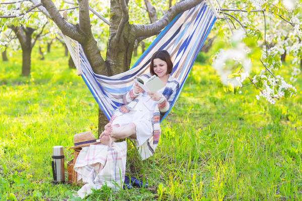 Beautiful pregnant woman sitting in hammock in blooming garden Stock photo © dashapetrenko