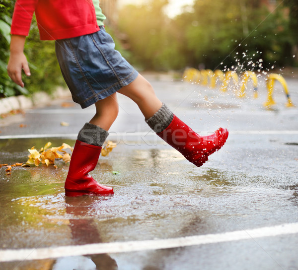 Child wearing red rain boots jumping into a puddle Stock photo © dashapetrenko