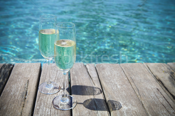 Champagne glasses by swimming pool Stock photo © dashapetrenko